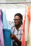 Male fashion designer looking at rack of clothes Stock Photography