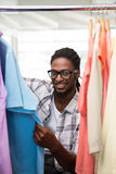Male fashion designer looking at rack of clothes Stock Image