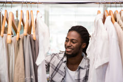 Male fashion designer looking at rack of clothes Stock Photo