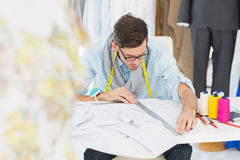 Male fashion designer working on his designs. Young male fashion designer working on his designs in the studio Royalty Free Stock Image