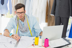 Male fashion designer working on his designs. Young male fashion designer working on his designs in the studio Royalty Free Stock Photo