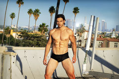 Male fashion model. Body portrait in natural light of a young male fitness model in black briefs on Los Angeles rooftop Royalty Free Stock Photography