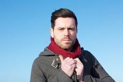Male fashion model holding winter jacket outdoors. Close up portrait of a male fashion model holding winter jacket outdoors Royalty Free Stock Photo