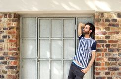 Male fashion model leaning against wall outdoors Stock Photography
