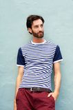 Male fashion model leaning against wall with striped shirt Stock Image