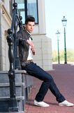 Male fashion model in leather jacket sitting outdoors Royalty Free Stock Photography