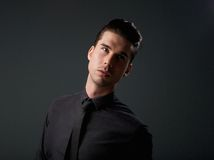 Male fashion model posing in black shirt and tie Stock Image