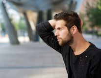 Male fashion model posing with hand in hair. Close up side view portrait of a male fashion model posing with hand in hair Royalty Free Stock Photo