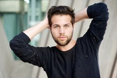 Male fashion model posing with hands behind head Royalty Free Stock Images