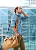 Male fashion model posing with leather bag Royalty Free Stock Images