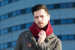 Male fashion model posing outdoors with jacket and scarf Stock Photo