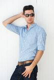 Male fashion model posing with sunglasses outdoors Stock Photo