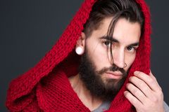 Male fashion model with scarf. Close up portrait of a male fashion model posing with red scarf on gray background Stock Photos
