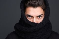 Male fashion model scarf covered face. Close up portrait of a male fashion model with scarf covered face stock photo