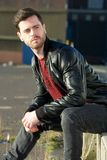 Male fashion model sitting outdoors with jeans and black jacket Royalty Free Stock Image