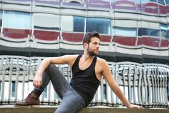 Male fashion model sitting outdoors in urban area Stock Images