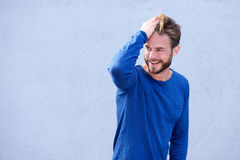 Male fashion model smiling with hand in hair Royalty Free Stock Image