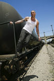 Male fashion model on train. Male fashion model posing outdoors on a train Royalty Free Stock Image