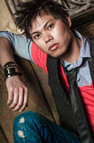 Male Fashion Model. Young guy male model. Asian man with spiked hair in trendy fashion clothing sitting in a night club booth. Wearing suit vest and tie Stock Photos