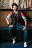 Male Fashion Model. Young guy male model. Asian man with spiked hair in trendy fashion clothing sitting in a night club booth. Wearing suit vest and tie Royalty Free Stock Image