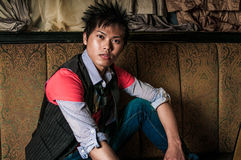 Male Fashion Model. Young guy male model. Asian man with spiked hair in trendy fashion clothing sitting in a night club booth. Wearing suit vest and tie Royalty Free Stock Photography