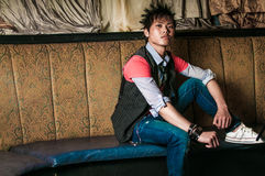Male Fashion Model. Young guy male model. Asian man with spiked hair in trendy fashion clothing sitting in a night club booth. Wearing suit vest and tie Stock Image