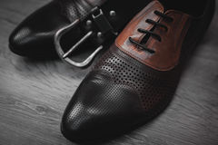 Shoes with belt on wooden background. Male fashion with shoes with belt on wooden background Royalty Free Stock Photos