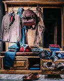 Male fashion stylish casual clothes in home wardrobe. Jacket, jeans, shirt, jumper, shoes, backpack Stock Image