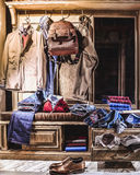 Male fashion stylish casual clothes in home wardrobe. Jacket, jeans, shirt, jumper, shoes, backpack Stock Photos