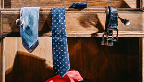 Male fashion stylish clothes in home wardrobe. Neckties and belts Royalty Free Stock Photography