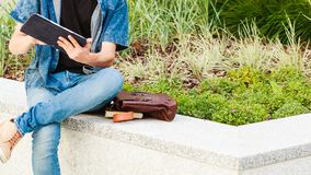 Guy with tablet sitting on ledge next to flowers. Male fashion, technology, student concept. Guy with tablet and bag full of notebooks wearing jeans outfit stock photo