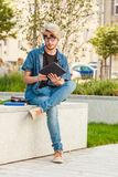 Hipster guy with tablet sitting on ledge Royalty Free Stock Photos