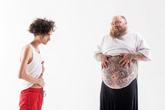 Male fatty boasting of his tummy to skinny guy. Joyful fat men is showing his tattooed belly to slim one and smiling. Thin boy is touching his abdomen and Royalty Free Stock Images