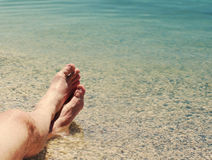 Male feet on a beach against the sea in a summer sunny day. Vacation at the sea Stock Images