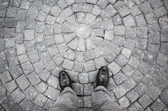 Male feet in black new shining shoes on stones. Male feet in black new shining shoes standing on old gray stone pavement with round pattern Royalty Free Stock Image