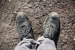 Male feet in black shoes standing on road mud Royalty Free Stock Image