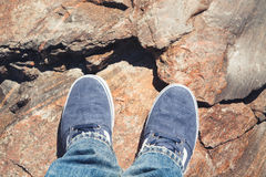 Male feet in blue canvas sport shoes on rock Royalty Free Stock Images
