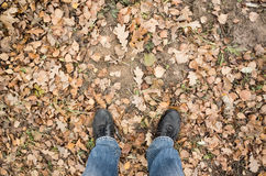 Male feet in blue jeans and black shoes on dirty ground Royalty Free Stock Image