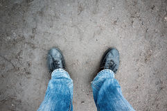 Male feet in blue jeans and black shoes on rural road Stock Images