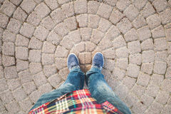 Male feet in blue jeans and sneakers. Standing on old gray stone pavement with round pattern Royalty Free Stock Images
