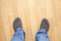 Male feet in blue pants and gray woolen socks Royalty Free Stock Images