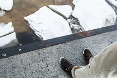 Male feet in boots against Ice floes on the river, texture. Danger ice concept. Royalty Free Stock Photo