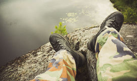 Male feet in camouflage pants. And black rough shoes. Travel lifestyle background. Vintage tonal correction photo filter, old style effect Stock Images