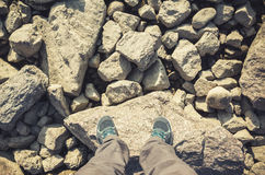 Male feet in canvas shoes stand on rocks Royalty Free Stock Photography