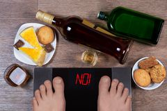 Male feet on digital scales with word no on screen. Bottles and glasses of alcohol, plates with sweet food. Concept of consequences of unhealthy lifestile royalty free stock photography