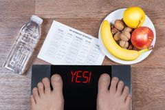 Male feet on digital scales with word yes surrounded by bottle of water, plate with healthy food and workout schedule paper. Royalty Free Stock Images
