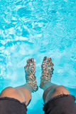 Male feet dipping in swimming pool Royalty Free Stock Images