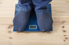 Male feet on the floor scales. The male feet on the floor scales Stock Photo
