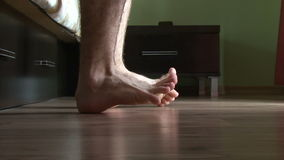 Male feet getting out of bed stock footage