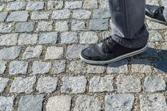 Male feet in gray jeans and sneakers standing on old stone pavement Stock Images